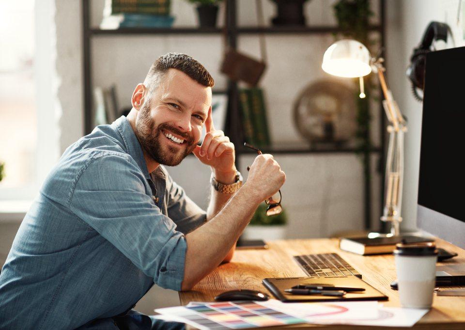 Mann sitzt lachend am PC