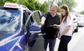 Fahrschullehrer erklärt Schülerin Fahrzeug