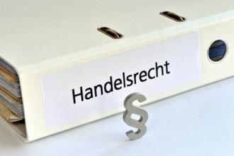 Ordner mit Aufschrift Handelsrecht und Paragraphen-Symbol
